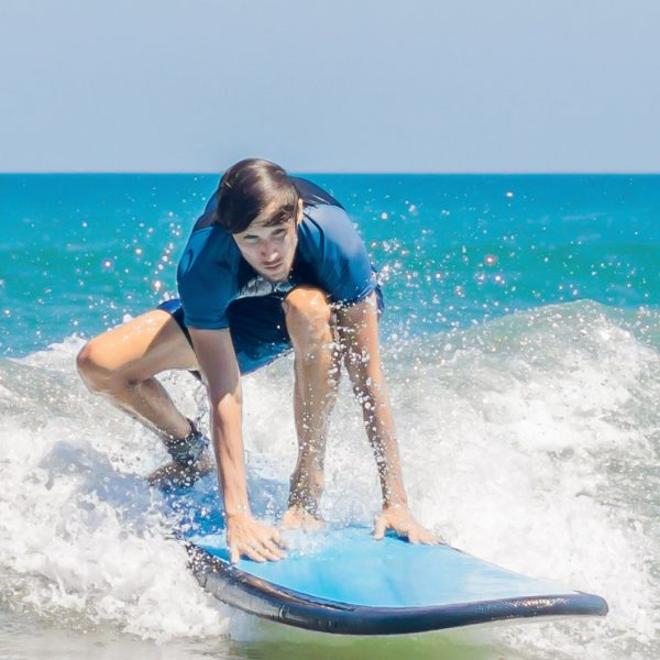 Young man, beginner Surfer learns to surf on a sea foam on the Bali island. BANNER, long format