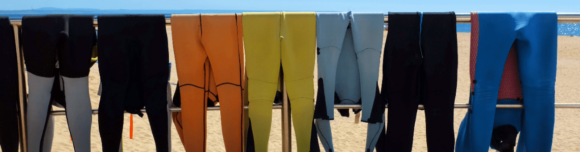 wetsuits drying at the beach